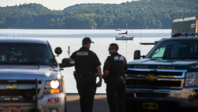 Police officers wait for the search for a missing boater to resume on Malletts Bay in Colchester on Thursday, June 16, 2016.  A crash between two motorboats on Wednesday injured one man and left one man missing.