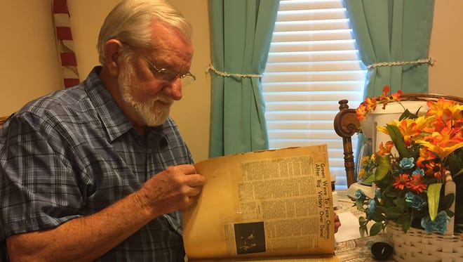 Keith Godfrey, a member of Easley High School's 1967 Class AA state championship football team, looks through a scrapbook with stories and photos from the season
