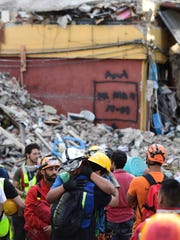 Rescue workers embrace each other after a seismic alert