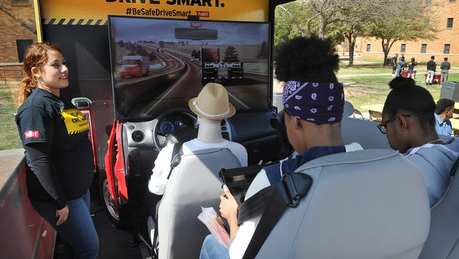 In this file photo, Wendy Rodriguez, left, of TxDOT operates a backseat driver simulation game at Midwestern State University. TxDOT reps will be at the farmers market Saturday with a virtual reality simulation showing the dangers of distracted driving.