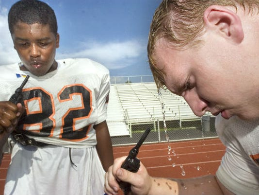 Alonzo Henderson, left, and Josh Hunt cool down during a water break on the first day of York Suburban football practice in August 2009. The PIAA Board of Directors is discussing ways to get players used to the heat before they participate in full-pad workouts during the hot days of football camp. (Daily Record/Sunday News -- File)