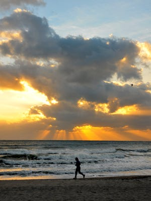 A jogger takes an early morning run at sunrise along Cocoa Beach.