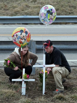 Elizabeth Napier and Jason May erect crosses during a vigil March 18 near where their 13-month-old twins were killed by a car. Police still haven't given a cause for the crash.