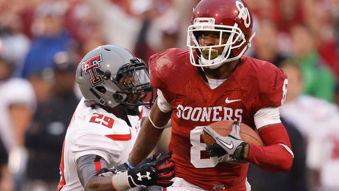 Oklahoma wide receiver Jalen Saunders (8) takes a Blake Bell pass past Texas Tech defensive back Olaoluwa Falemi (29) for a touchdown in the second quarter Saturday in Norman, Okla.