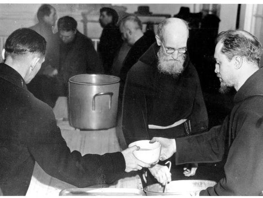 Father Solanus Casey serves soup in 1941, Casey is one of the co-founders of the Capuchin Soup Kitchen. He ministered in Detroit during the Great Depression and helped serve soup and bread to those in need.