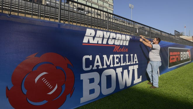 This file photo shows Lee Trucks of CSE Graphics installing signage for the Raycom Media Camellia Bowl at Cramton Bowl in December. Montgomery Mayor Todd Strange said that last December, there was approximately $25 million more that was spent in the city as opposed to December 2013, with the bowl game heavily contributing to that increase.