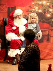 A young girl takes a photo with Santa Claus Saturday