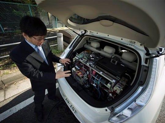 El director general de Nissan Motor Co., Tetsuya Iijima, explica al funcionamiento del prototipo de un vehículo autónomo tras una prueba de conducción en Tokio, el 3 noviembre de 2015. (Foto AP/Eugene Hoshiko)
