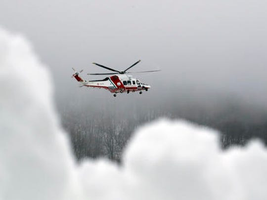 A Coast Guard rescue helicopter flies to the avalanche-hit area where a hotel is buried under the snow, near Farandola, central Italy, Friday, Jan. 20, 2017. Rescue crews located up to eight people alive in the kitchen of an avalanche-crushed hotel on Friday, an incredible discovery that boosted spirits two days after the massive snow slide buried around 30 people in the resort.