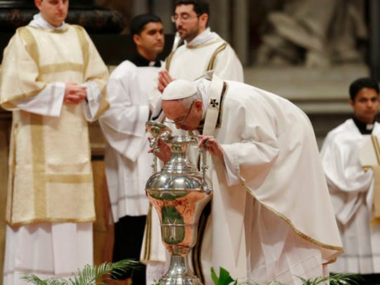 Pope Francis blows inside an amphora containing holy oil during a Chrism Mass in St. Peter's Basilica at the Vatican Thursday, April 13, 2017. During the Mass the Pontiff blesses a token amount of oil that will be used to administer the sacraments for the year.