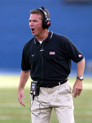 Utah coach Urban Meyer hollers to his team during a game against Utah State on Sept. 18, 2004.