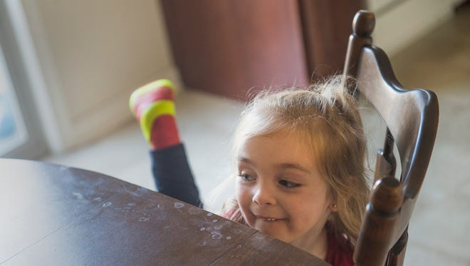 Alaina Crone, 3, of Hanover, pulls herself up to the kitchen table at her home in Hanover on Nov. 15, 2016. Crone has arthrogryposis multiplex congenita, a congenital illness that contracts the joints.