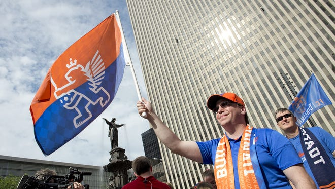Thousands of FC Cincinnati Soccer fans gathered on Fountain Square on Tuesday, May 29, 2018 to watch a live broadcast from Rhinegeist Brewery announcing that the team was accepted into Major League Soccer. Doug Alcorn of White Oak holds his FC flag high as he watches the jumbotron screen for the announcement.