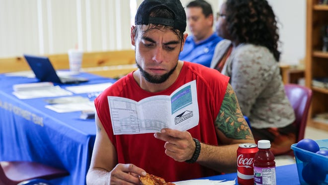 Dustin Halvorson, who had been living in the tent city under the Houston Harte Expressway, reads a pamphlet about the Housing Authority during a social service assessment event Friday, June 2, at the Salvation Army.
