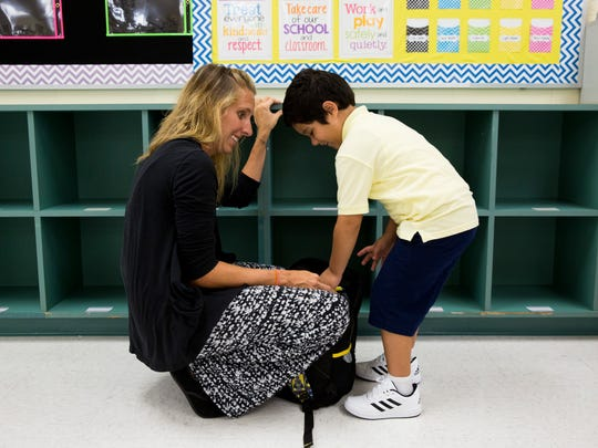 Alicia Macintyre, a first-year kindergarten teacher at Corkscrew, helps Mauricio Pimienta, 5, with putting away his backpack as young students began their first day of school at Corkscrew Elementary on Wednesday, Aug. 16, 2017, in Golden Gate Estates.