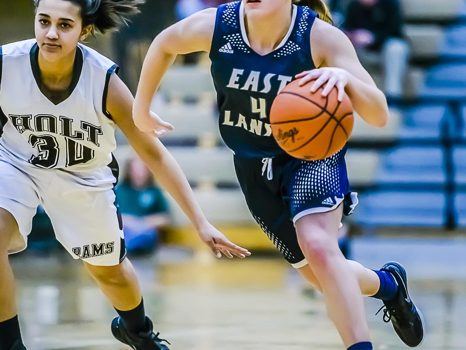 Taryn McCutcheon ,right, of East Lansing drives past Avi'onna Huxstable of Holt during their game Friday January 15, 2016 in Holt. KEVIN W. FOWLER PHOTO