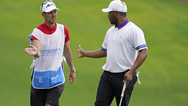 Harold Varner III celebrates with his caddie on the 18th green after finishing the first round of the Wyndham Championship golf tournament at Sedgefield Country Club on Thursday, Aug. 13, 2020, in Greensboro, N.C.