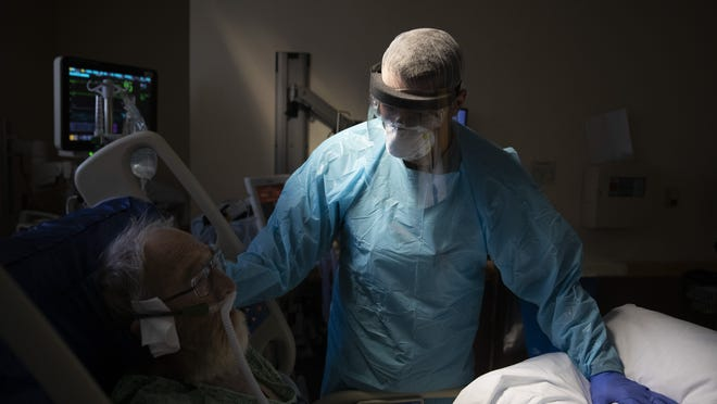 Spencer Cushing, 29, tends to David Feinour, a 71-year-old COVID-19 patient, at St. Jude Medical Center in Fullerton, Calif., in July.  The worldwide death toll from the coronavirus has eclipsed 1 million, nine months into a crisis that has devastated the global economy and forced multitudes to change the way they live, learn and work.