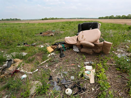 Discarded furniture is among the items dumped in a field off County Road E 150 S Monday, May 14, 2018, just east of Lafayette.