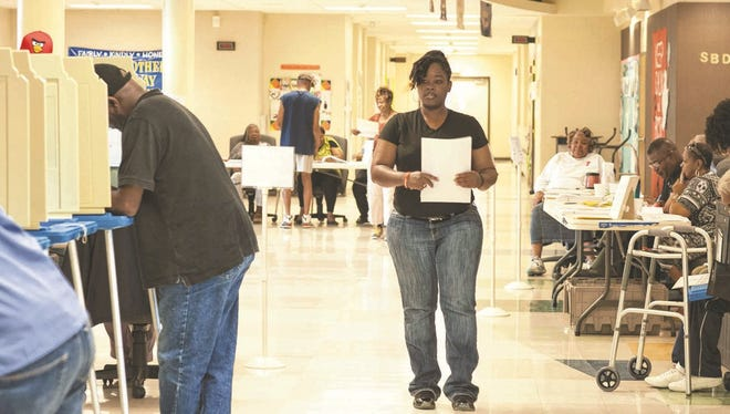 Tija Jackson walks toward a polling booth at Carter Traditional Elementary School on Tuesday.