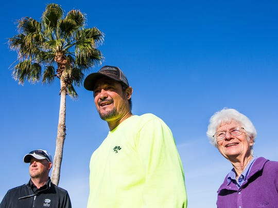 A cat stuck in this palm tree on the Oakwood Golf Course in Sun Lakes for almost a week, was finally saved by being forced to jump down.  Involved in the rescue were, (from left) Chris King, Norcy Techer and Barb Butler.