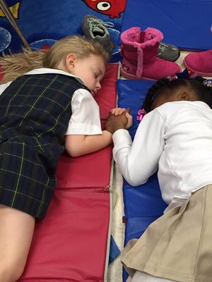 Two girls hold hands during nap time at Presbyterian Day School in Clarksdale, Miss.