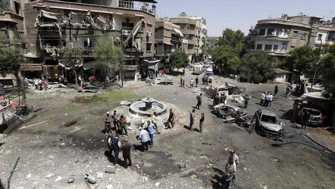 Syrians inspect the site of a suicide bomb attack in the capital Damascus' eastern Tahrir Square district, on Sunday.