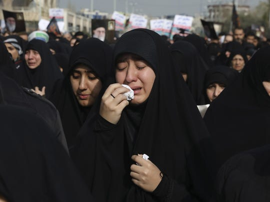 "A women weeps while mourning during a demonstration over the U.S. airstrike in Iraq that killed Iranian Revolutionary Guard Gen. Qassem Soleimani, in Tehran, Iran, Jan. 3, 2020. Iran has vowed ""harsh retaliation"" for the U.S. airstrike near Baghdad's airport that killed Tehran's top general and the architect of its interventions across the Middle East, as tensions soared in the wake of the targeted killing. (AP Photo/Vahid Salemi)"