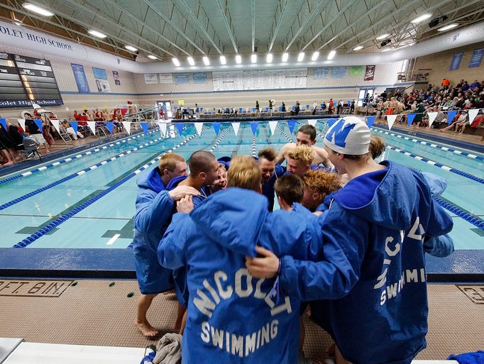 The Nicolet boys swim team gathers for a cheer before