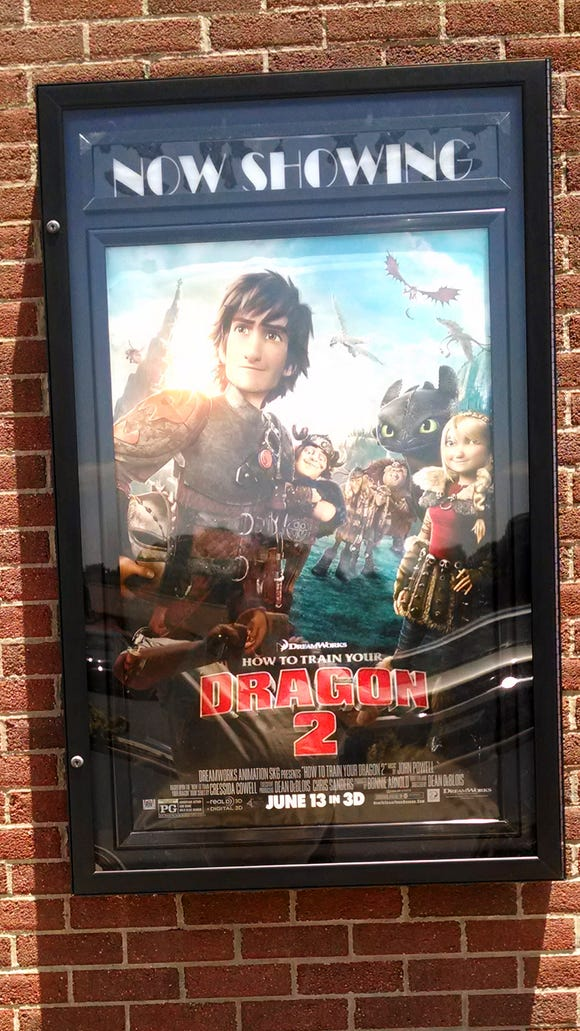 "A movie poster for ""How to Train Your Dragon 2"" hands in a ""Now Showing"" display case at Zeus Theater in Waynesboro."
