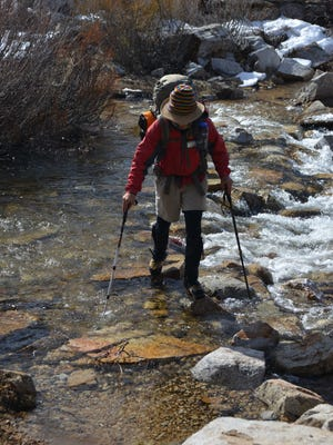 A hiker uses proper technique to cross Tyndall Creek in Sequoia National Park in May, 2014.
