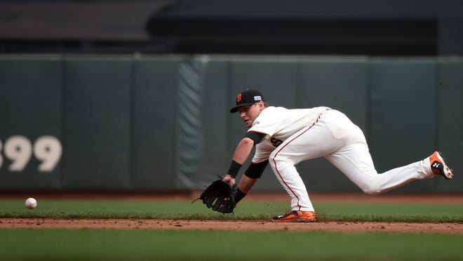 Oct 14, 2014; San Francisco, CA, USA; San Francisco Giants second baseman Joe Panik (12) dives for a ground ball hit during the third inning against the St. Louis Cardinals in game three of the 2014 NLCS playoff baseball game at AT&T Park. Mandatory Credit: Kyle Terada-USA TODAY Sports