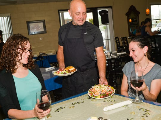 Aristos Anastassiades, owner of Poseidon's Greek Restaurant on Kaliste Saloom serving customers Nicky Guillot (L) and Andrea Broussard. June 17, 2016.