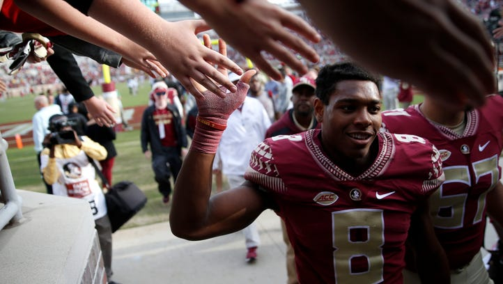 FSU's Jalen Ramsey high fives fans after giving away his game gloves, worn while beating NC State 34-17 at Doak Campbell Stadium on Saturday.