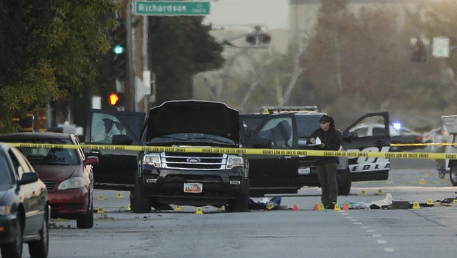 An investigator looks Thursday at the SUV that was involved in a police shootout with the suspects in Wednesday's mass shooting in San Bernardino, Calif.