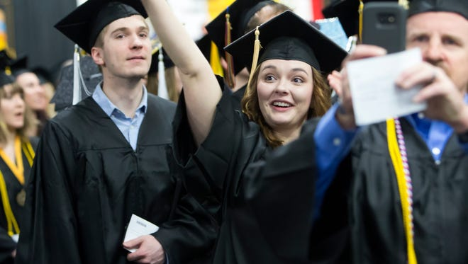 Amanda Koeppel waves to the audience while waiting to receive her diploma during the University of Wisconsin-Oshkosh commencement ceremony at the Kolf Sports Center on Saturday, May 14, 2016.