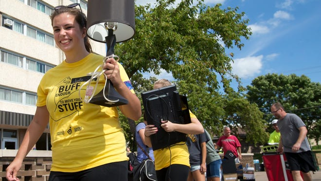 Joelle Lindemann carries a lamp while volunteering for the move in day at University of Wisconsin-Oshkosh in 2016. Thousands of students are moving to the Oshkosh campus over Labor Day weekend.