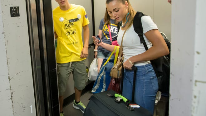 Shea Hill rolls her luggage into the elevator Sunday at South Scott Residence Hall at the University of Wisconsin-Oshkosh Campus.