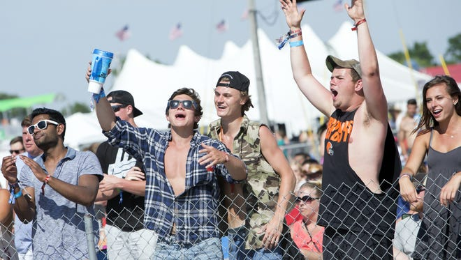 A group of friends roar as the band Locash plays at Country USA at Ford Festival Park in June 2016.