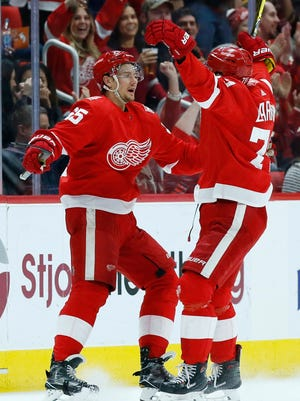 Red Wings defenseman Danny DeKeyser, left, celebrates his goal against the Hurricanes with teammate Dylan Larkin during the first period on Saturday, Feb. 24, 2018, at Little Caesars Arena.