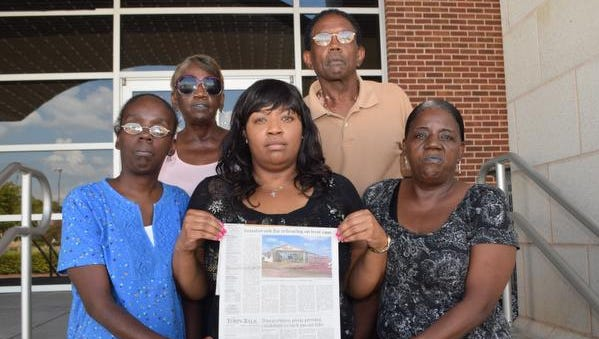 The family of Vivian Culbert Chaney, who was murdered in 1985 with her daughter, brother and boyfriend, hold a Town Talk article with a story about the man convicted in the murders. Nathaniel Code Jr. is among three Angola death row inmates who have sued over hot conditions at the prison. The family is upset that Code's sentence hasn't been carried out and say he doesn't deserve better conditions. The family members are Tomika Chaney (left, blue blouse), the daughter of Vivian Chaney and a survivor of the murders; Shirley Culbert-Johnson (center, bottom), sister of Vivian Chaney who found the victims; Kela Culbert-Barraka (far right, bottom), Barabara Culbert (back, far left) and Albert Culbert, Jr., all siblings of Vivian Chaney.