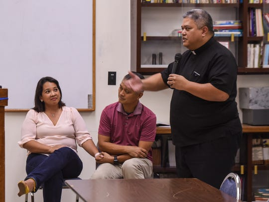 Couple, Christine and Richard Rosario, seated, hold each others hand as Father Jeff San Nicolas talks about marriage ministries within the island's Catholic community, during a briefing at the St. John Paul the Great Center for Evangelization on Wednesday, Aug. 2, 2017. On the date of the briefing, the Rosario's celebrated their 20th wedding anniversary.