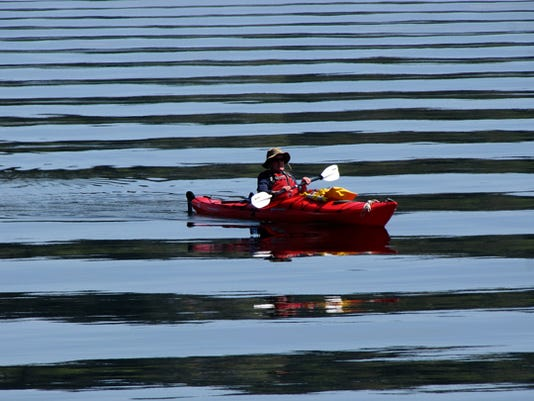 Jim Deighan, of Bremerton, drifts in his kayak towards Bachmann Park in Manette on a clear, calm Wednesday. (LARRY STEAGALL / KITSAP SUN)