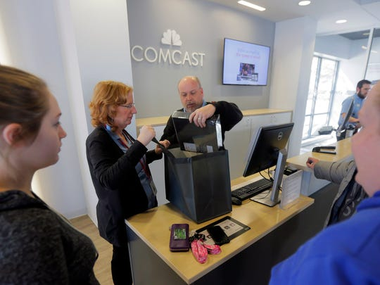 Comcast Xfinity store employees John Knotwell and Wendy Evegan pack some cable boxes up for customers at the new Hooper Avenue store in Toms River Thursday.