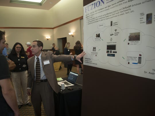 Anthony Ricco explains his Fuzion method to attendees at a Rowan University science fair Friday.