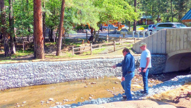 Ruidoso Public Works Director J. R. Baumann inspects the situation at  First Bridge on Main Road with the owner of a nearby lodging business.