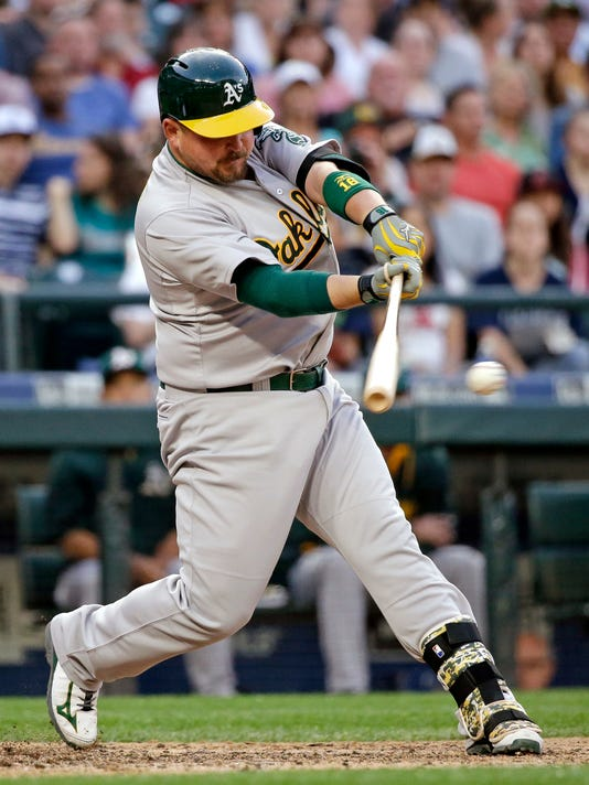 Oakland Athletics' Billy Butler singles in a run against the Seattle Mariners during the fifth inning of a baseball game Saturday, May 9, 2015, in Seattle. (AP Photo/Elaine Thompson)