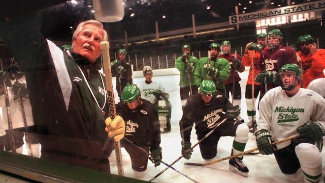 -  -MSU hockey coach Ron Mason, left, diagrams a play for his team during a practice Monday.