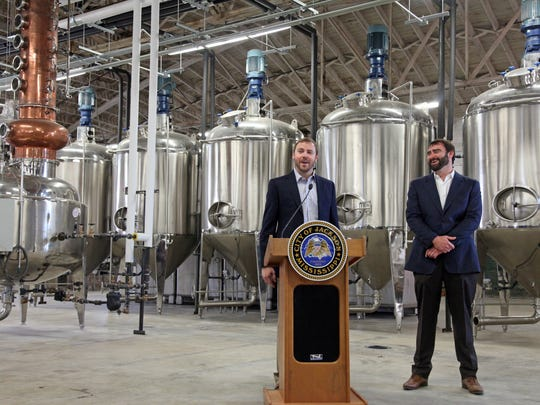 Cathead Distillery co-founders Richard Patrick, left, and Austin Evans speak Tuesday at a ribbon cutting for their new location on South Farish Street.