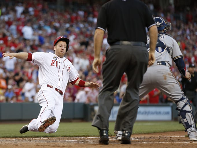 Cincinnati Reds third baseman Todd Frazier (21) scores on a double by first baseman Joey Votto (19) against the Milwaukee Brewers at Great American Ball Park.